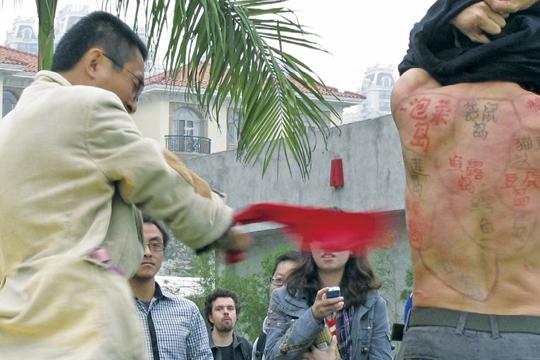 """2010年,第一届""""广州·现场"""",越南艺术家陈龙在作品中邀请观众用红领巾鞭刷去其身上的一个虚构的岛屿,然后可取走漂在水池上的同名蛋糕。在展演途中被策展人干预,终止了作品。"""
