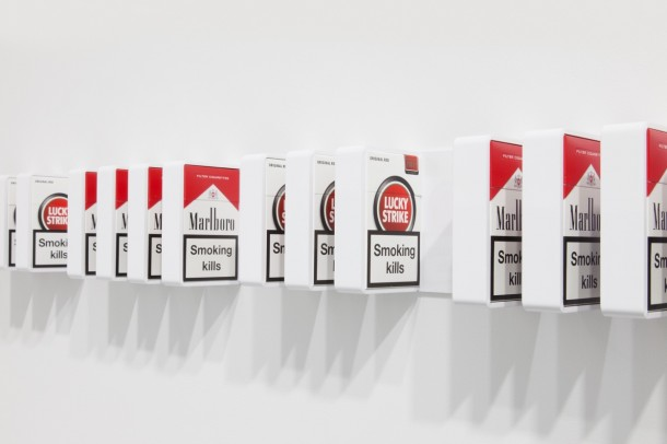 Detail of PMBTI, 2014, Exchange of common stock, certificate, powder-coated aluminum, cigarette packs, 3 25/32 x 53 3/8 x 2 15/32 in. (9.6 x 135.6 x 6.3 cm.) (sculpture) 14 x 10 1/2 in. (35.6 x 26.7 cm.) (certificate) Courtesy of the artist