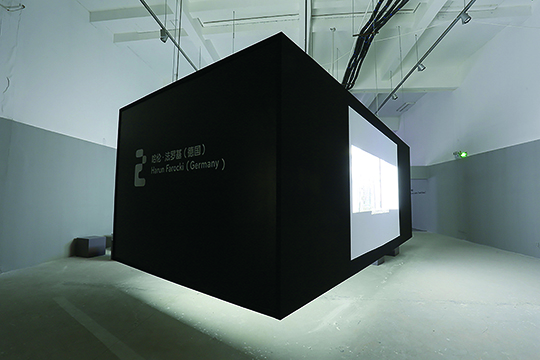 Installation view of three projected works of Harun Farocki