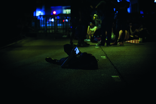 Student lying on the street playing with a mobile phone PHOTO: Manson Wong