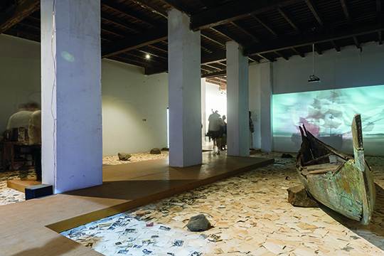 Dinh Q Lê, Erasure, single-channel HD video with color and sound, 7 min. Found photographs, stone, wooden boat fragments, computer, scanner, website