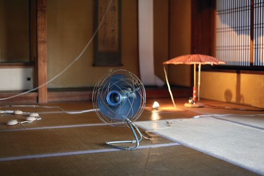 Circus in the Ground, 2014 Compass, fossil, chime, bell, garden funiture, feather duster, ruler, light, umbrella, gut, motor, light bulb, roll paper, approx. 250 x 1200 x 1200 cm PHOTO: Yuko Mohri