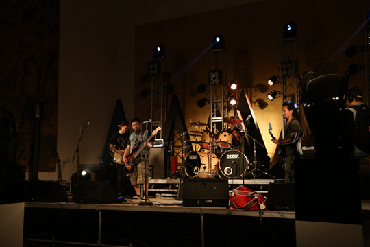 """""""Orbit of Rock"""",2014 Zhang Ding recreates a classic rock concert that took place in Moscow's Red Square in 1991. In this recital, four bands perform 13 songs. The scene uses black statues and golden, mottled wall hangings as decoration."""