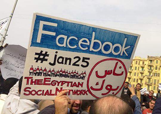 """2011年埃及抗议者高举呼喊脸书的标语 镜头之下的抗议从来都不是单纯的示威,而是随时可能引发另一场抗议的表演。 脸书这样的网络媒介不但打破了在固定场所和时间才能明确显现的""""观看-表演""""关系,也将其原有的仪式感分解为日常生活中反反复复的行为模式——新的""""仪式""""确认了当代生活的意义。"""