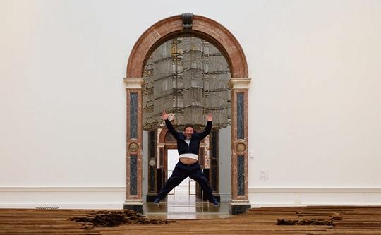 Ai Weiwei pose pour les photographes devant son oeuvre Straight durant une visite presse de sa retrospective à la Royal Academy de Londres, 15 septembre 2015 , photographie de Leon Neal, source AFP