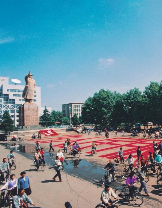 """1992年9月18日, 庄辉在洛阳轴承厂广场书写并张贴""""为人民服务""""的标语。"""