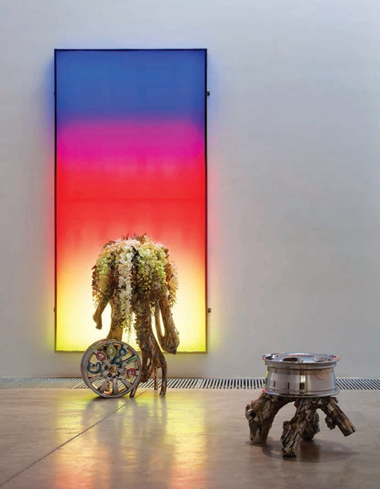 《日落》,2012年,LED灯箱、假花、彩色金属、汽车轮胎、树脂 灯箱:308 × 158厘米;车轮和树凳:55 × 55 × 80厘米;车轮和假花:60 × 60 × 115厘米