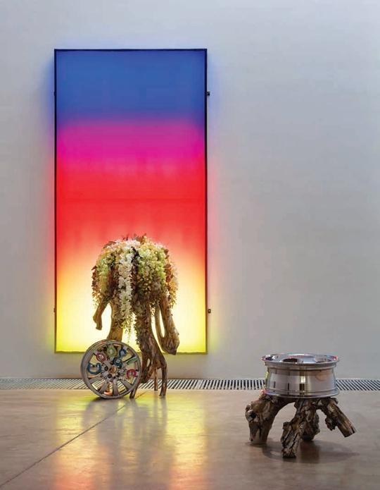 The Sunset, 2012 Boite lumineuse LED, fleurs artificielles, métal coloré, pneu, résine Boite lumineuse 308 x 158 cm, roue et chaise en bois  55 x 55 x 80 cm, roue et fleurs artificielles 60 x 60 x 115 cm Avec l'aimable autorisation de la galerie Kraupa-Tuskany Zeidler et de l'artiste
