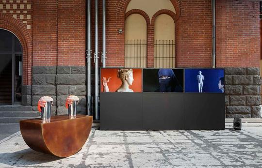 """""""一些事情发生了继续发生""""展览现场,ABC柏林当代艺术博览会,2014年 左:《滚动的节奏》,2014年,彩铜、汽车轮胎,127 × 48 × 22 厘米 右:《行动》,2014年,三频录像,10分钟"""